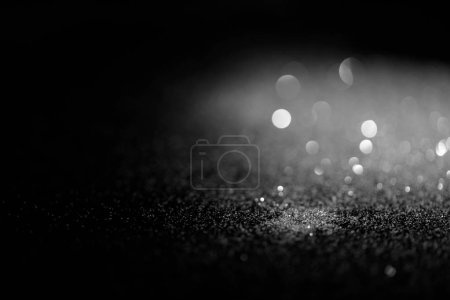 blurred shiny silver glitter on dark background