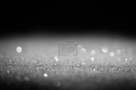 sparking silver glitter with sparking bokeh on black background