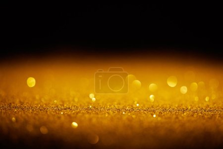 sparking gold glitter with bokeh on black background
