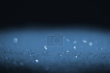 sparking blue glitter with bokeh on black background