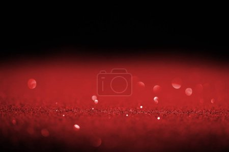sparking red glitter with bokeh on black background