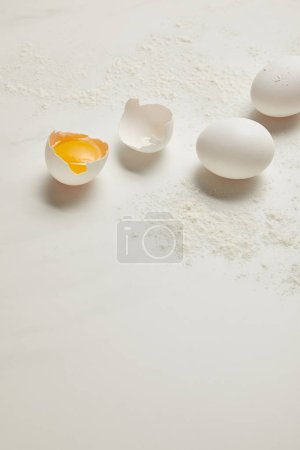 close up view of raw chicken eggs and flour on white marble tabletop