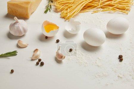 Photo pour Bouchent la vue de macaroni non cuits et ingrédients pour la pâte sur une surface blanche - image libre de droit