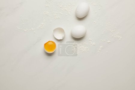 top view of raw chicken eggs and flour on white marble tabletop
