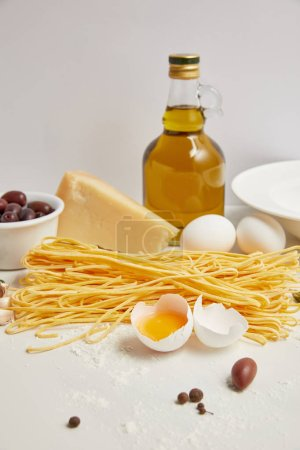 close up view of arranged ingredients for cooking italian pasta on white tabletop