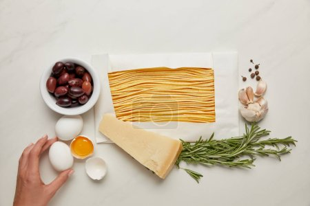 Photo for Partial view of woman and italian pasta ingredients on white marble tabletop - Royalty Free Image