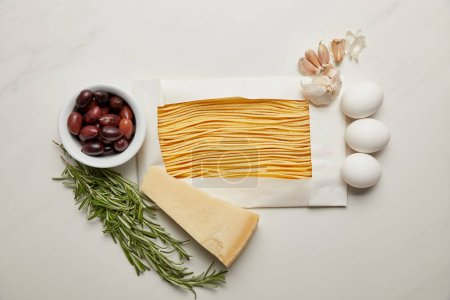 Photo for Top view of assorted uncooked macaroni, rosemary, cheese, garlic and raw chicken eggs ingredients for pasta on white marble surface - Royalty Free Image