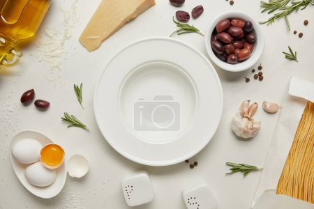 flat lay with empty plate and pasta ingredients on white marble surface