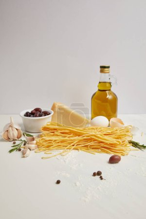close up view of olive oil, uncooked macaroni, rosemary and cheese for cooking pasta on white tabletop