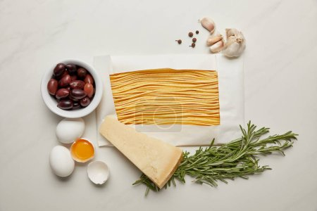Photo for Flat lat with assorted italian pasta ingredients arranged on white marble surface - Royalty Free Image