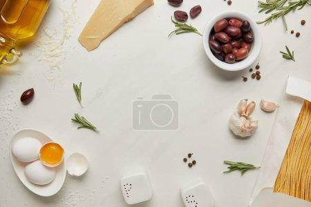 lat plana con ingredientes de pasta italiana surtidos dispuestos en la superficie de mármol blanco