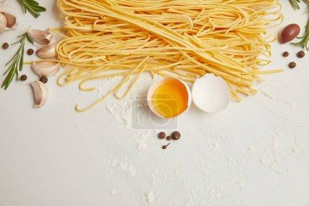 Photo pour Vue de dessus de macaroni non cuits, oeuf de poulet cru, poivre noir et romarin disposées sur la surface blanche - image libre de droit