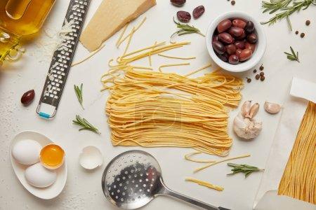 Photo pour Plat étendre avec des ingrédients de pâtes italiennes, louche et râpe disposée sur la table blanche - image libre de droit