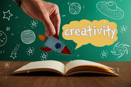 "cropped view of teacher holding rocket over open book with ""creativity"" lettering"