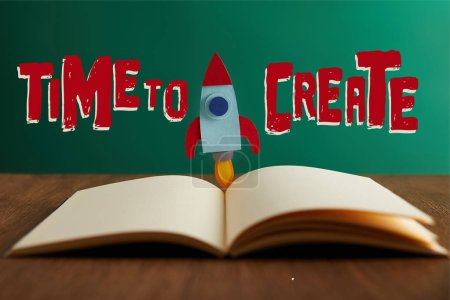 "open book with colorful rocket on wooden table with ""time to create"" lettering"