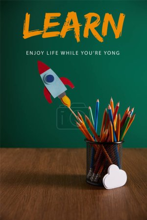 """colorful pencils, rocket, cloud sign on wooden table with chalkboard on background with """"learn - enjoy life while you are young"""" lettering"""