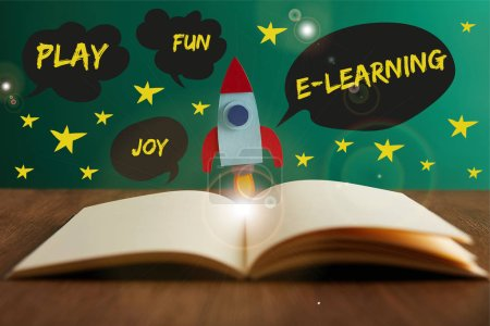 open book with colorful rocket on wooden table with play, joy, fun and e-learning words