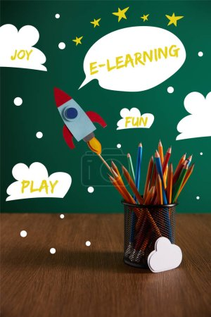 colorful pencils, rocket, cloud sign on wooden table with chalkboard on background with play, joy, fun and e-learning words
