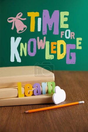"books, pencil, cloud sign and learn lettering on wooden table with ""time for knowledge"" lettering"