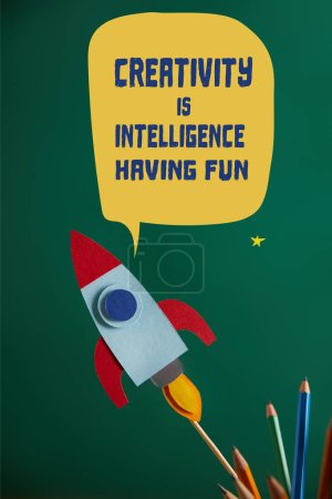 "pencils and colorful rocket on green chalkboard with ""creativity is intelligence, having fun"" lettering"