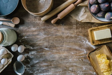 Photo for Top view of messy wooden table with spilled flour and baking ingredients - Royalty Free Image