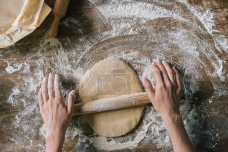 abgeschnittene Aufnahme einer Frau, die Teig mit Nudelholz auf rustikalem Holztisch zubereitet