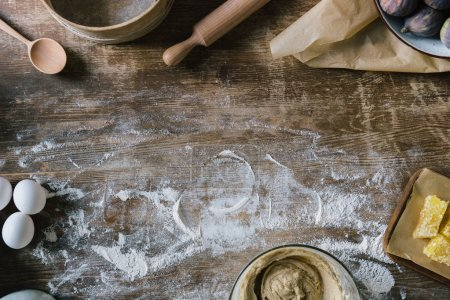 Photo for Top view of messy rustic wooden table with spilled flour and baking ingredients - Royalty Free Image