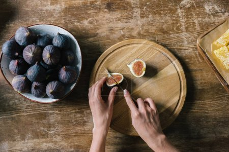 Photo for Cropped shot of woman cutting fig on rustic wooden table - Royalty Free Image