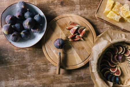 pile of figs in bowl and on cutting board on rustic wooden table during pie preparation