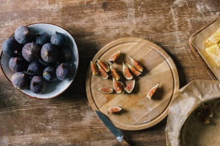 pile of ripe figs in bowl and on cutting board on rustic wooden table during pie preparation
