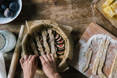 cropped shot of woman preparing delicious fig pie on rustic wooden table