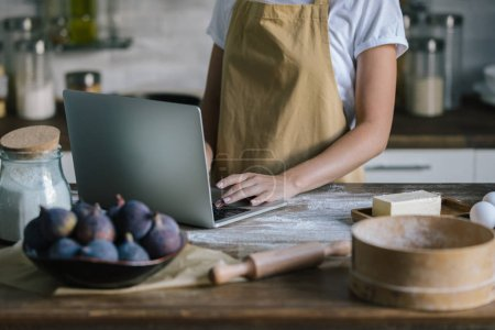 Photo for Cropped shot of woman using laptop during pie preparation - Royalty Free Image