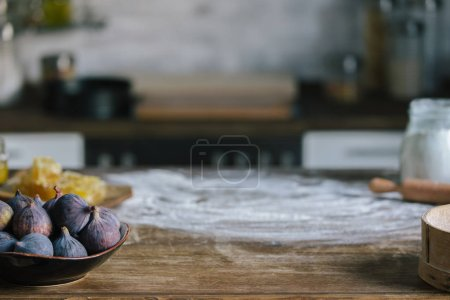 close-up shot of figs pie ingredients on rustic wooden table covered with flour