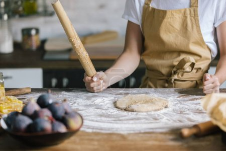 cropped shot of woman with rolling pin preparing dough for pie on rustic wooden table