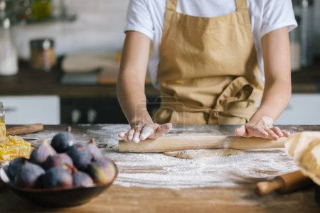 cropped shot of woman preparing dough for pie on rustic wooden table