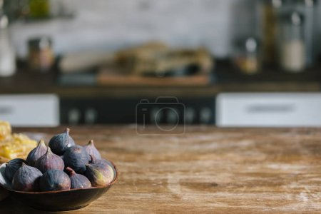 close-up shot of bowl with ripe figs standing on rustic wooden table