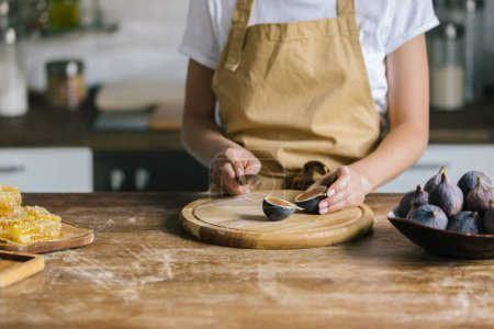 cropped shot of woman cutting figs on rustic wooden table