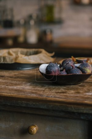 close-up shot of bowl of fresh figs on rustic wooden table