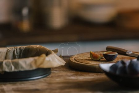 Photo for Figs with cutting board and baking form for pie on rustic wooden table - Royalty Free Image