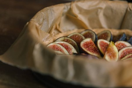 sliced figs in baking tray with parchment paper on rustic wooden table