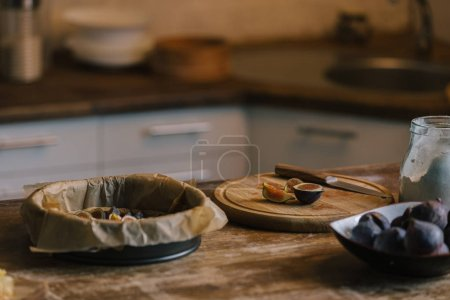 Photo for Pile of figs with cutting board and baking form for pie on rustic wooden table - Royalty Free Image