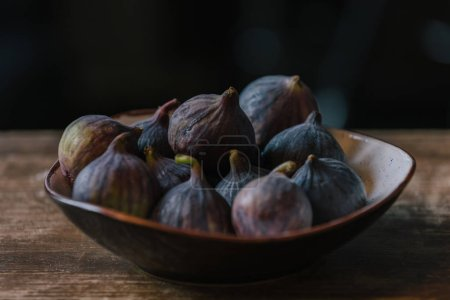 close-up shot of heap of figs in bowl on rustic wooden table