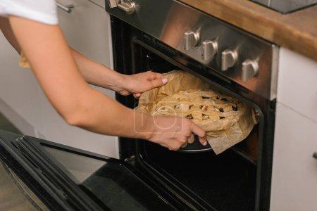 recadrée tir de femme mettant la tarte dans le four
