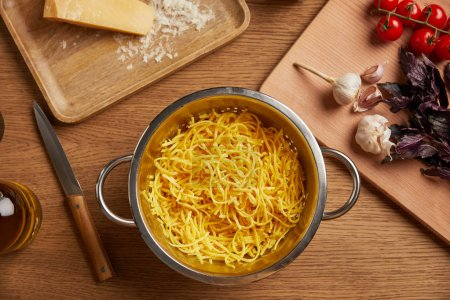 cooked spaghetti in metal colander surrounded with ingredients for pasta on wooden table