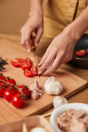 cropped shot of woman cutting cherry tomatoes for pasta