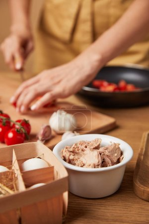 cropped shot of woman cooking pasta with bowl of chicken meat on foreground