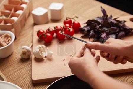 cropped shot of woman cutting garlic for pasta