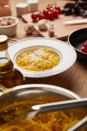 close-up shot of plate on spaghetti surrounded with ingredients on wooden table