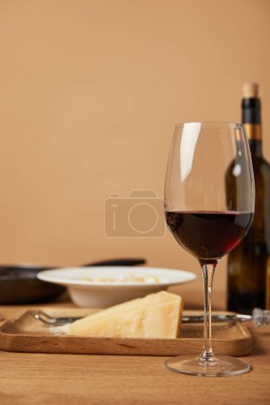 glass and bottle of red wine and grated parmesan for pasta on wooden table
