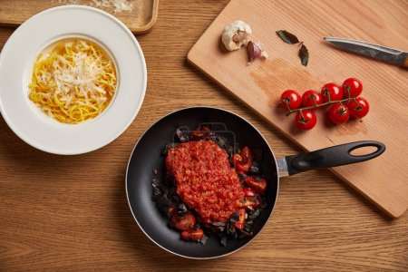 top view of plate of spaghetti and tomato sauce in frying pan on wooden table